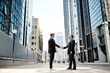 two businessmen shaking hands on background office buildings