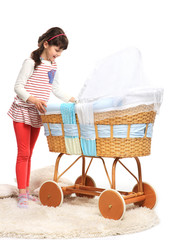 Cute young girl looking at baby sleeing in retro style crib