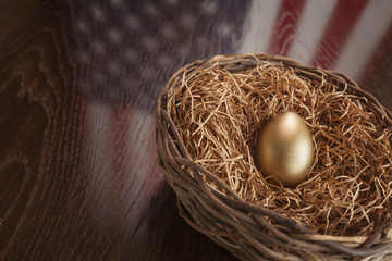 Golden Egg in Nest with American Flag Reflection on Table