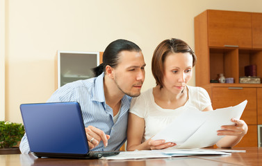 couple staring financial documents at table in home
