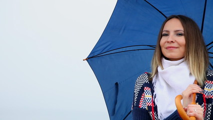 Smiling woman with blue umbrella winking outdoor