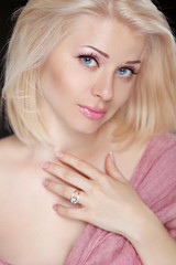 Beautiful blond young woman with pretty makeup, posing at camera