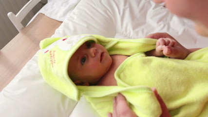 cute infant wrapped in a towel after bath