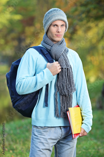 Male student holding books on a cold day in park