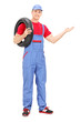 Mechanic holding a tire and gesturing with hand