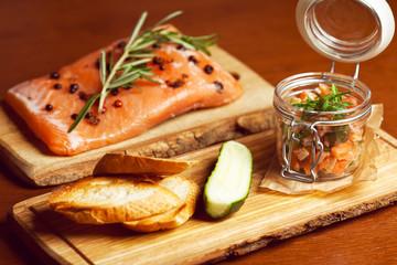 Mason jar with salmon, cucumber, toasts and herbs