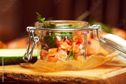 Mason jar with salmon, cucumber, toasts and ruccola
