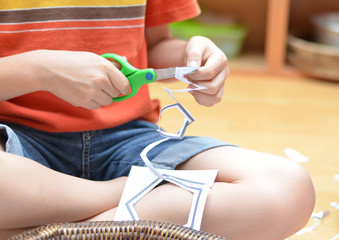 Little hand's boy cutting paper montessori materials