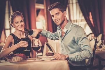 Couple with glasses of red wine in luxury restaurant