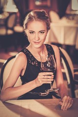 Girl with glass of red wine alone in a restaurant