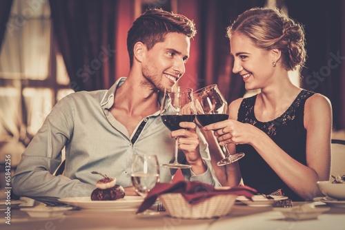 Leinwandbild Motiv Couple with glasses of red wine in luxury restaurant