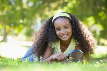 Young girl holding magnifying glass in the park smiling at camer