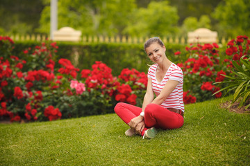 girl sitting on the grass in the Park summer green.