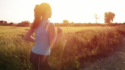 Female Jogger Woman Running at Sunset Listening to Music