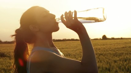 Attractive Young Female Model Drinking Water Bottle Sunset