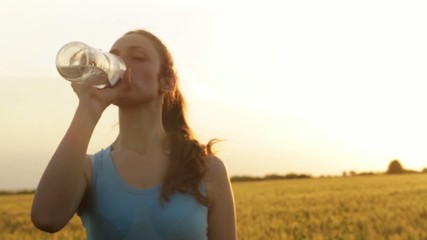 Athletic Female Model Drinking Water Summer Field Sunset