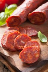 spanish chorizo sausage with basil on chopping board