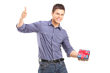 Young man holding a present and giving thumb up