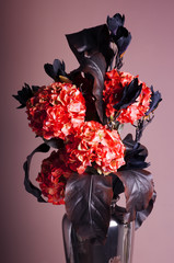 bouquet of red hydrangea and dark blue magnolia in a vase