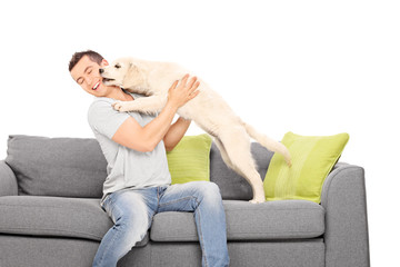 Man playing with a puppy seated on sofa