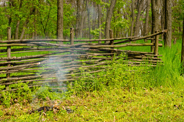 Small fire burning alongside a rustic wooden fence