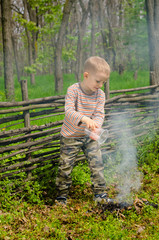 Little boy putting out a camp fire