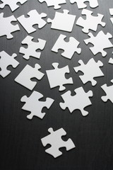 Blank white jigsaw pieces scattered across a blackboard