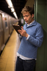 Young caucasian man using tablet pc in subway station