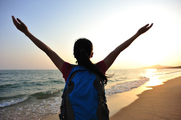 cheering woman hiker open arms at sunrise seaside beach  open be