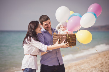 Happy family on the beach with ballons and basket