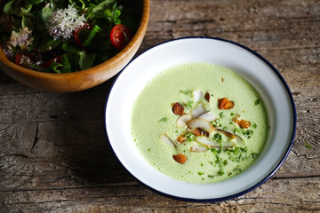 Green pea creamy soup with coconut and nuts, salad