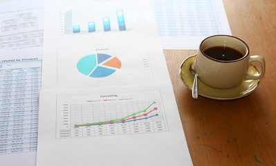 forcasting and analyzing incomes charts, graphs with coffee cup,