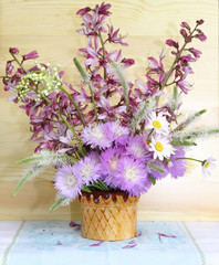Lovely bouquet of wild wildflowers is in a vase on a wooden wall