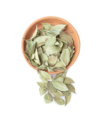 Dried bay leaves in a clay bowl isolated on white