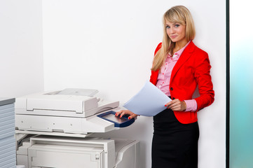 business woman with documents standing next to printer