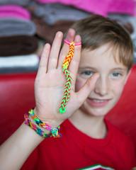 Enfant fabriquant des bracelets en élastique
