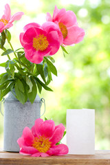 Pink peonies in metal vase and empty card for letter