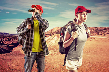 Young trekking couple with binocular in the desert.