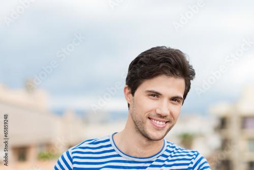 canvas print picture lächelnder sympathischer mann in der stadt