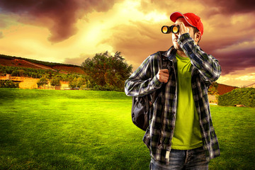 Man traveler looking in binocular standing on green valley