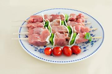 brochettes de viande crues présentées sur assiette