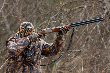 hunter in camouflage takes aim from a gun