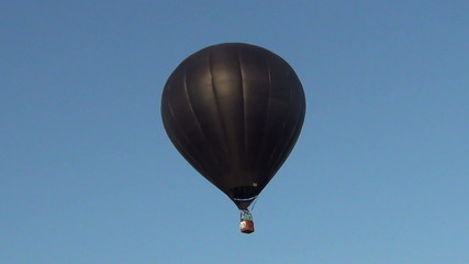 Black hot air balloon against blue sky