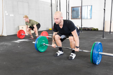 Group trains deadlift at crossfit center