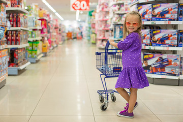 Little fashion girl with trolley in a large shopping center