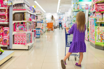 Back view of fashion girl with trolley in kid shopping center