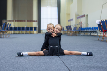 Two little gymnasts in the gym doing twine