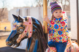 Little adorable girl on carousel at sunny day outdoor poster