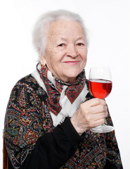 Pretty old woman with glass of wine