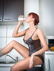 Attractive sexy woman in lingerie drinking milk in kitchen